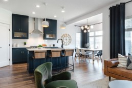 Kitchen area connected to living room with d=navy cabinets, leather and green velvet furniture and hardwood floors. The Lusitano Showhome by Pacesetter Homes in Jensen Lakes community St. Albert