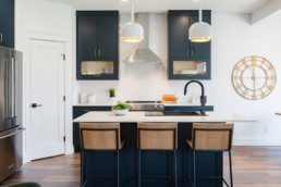 Kitchen with Navy blue modern cabinets light wood and black wire barstools with golden wall designs. The Lusitano showhome by Pacesetter Homes in Jensen Lakes St. Albert