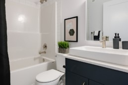 Bathroom with white countertops and shower, navy cabinets and gold faucets and light fixtures. Pacesetter Showhomes.