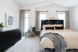 Master Bedroom with navy and gold accent decorations and grey curtrains. Pacesetter Homes Showhomes in St. Albert