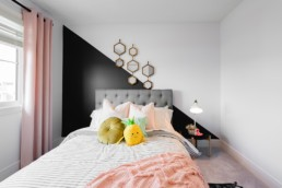 Secondary showhome bedroom with pink accent colors and black with geometric gold wall decorations, baby pink curtrains. Pacesetter Homes in Jensen Lakes