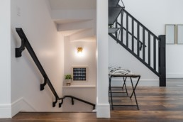 Staircase with black rails and trim in the Lusitano showhome in Jensen Lakes St. Albert