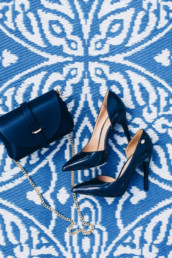Elegant leather classic women's blue shoes and a stylish leather blue women's bag with a golden strap on a creative blue carpet and white wooden floor. Stylish image of trendy blue women's summer heels.