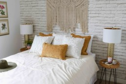Secondary bedroom in Cobalt beach showhome Jensen Lakes. White brick wallpaper with woven wall decorations and queen bed with gold and white pillows.