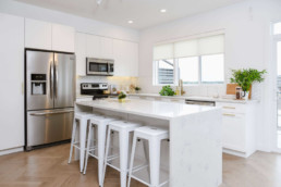 White kitchen with marble countertops and white tile. Kitchen plants. Cobalt Beach Showhome in Jensen Lakes St. Albert