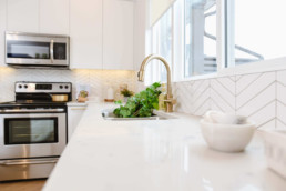 Gold sink with greens. Geometric white tile on adjacent to white marble countertop and oven. Jensen Lakes Cobalt Beach showhome in St. Albert