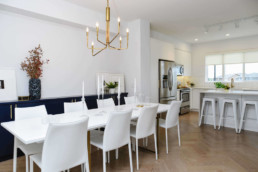 Dining room with white table and white leather chairs, connected kitchen with geometric white tile and white stools, hardwood floors and golden lights. Cobalt Beach showhome Jensen Lakes St. Albert