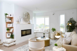 Living area with beige couch and modern classy gold accent decor, window reading nook with white pillows and large windows. Cobalt Beach Showhome in Jensen Lakes St. Albert
