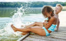Two kids splashing by lake, boy and girl on dock playing by the water.