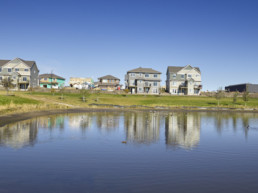 Community amenities in Jensen Lakes, homes by storm pond on sunny day
