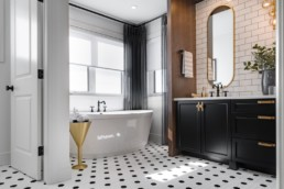 Black tile floor with mid-century modern decor bathroom with stand alone bathtub and golden decor accents. In Augusta Executive collections by Pacesetter homes in Jensen Lakes.
