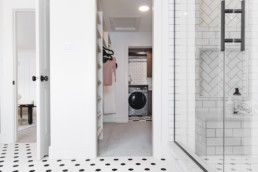 Modern vintage laundry room with black and white tile flooring and walls. In Jensen Lakes Showhomes.