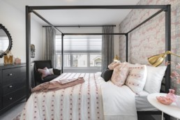 Secondary bedroom with pink interior design, gold light fixture and patterned pink wall, black wire framed bed. In Jensen Lakes St. Albert, Pacesetter Estate homes.