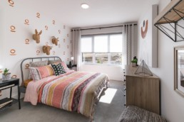 Secondary bedroom with colorful patterned decor and animal wall paper decals, light wood finishing and polka dot curtains. In Jensen Lakes Pacesetter homes showhome.