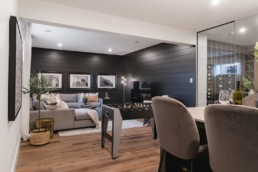 Den and wine area with black wooded walls a wine room, fooseball table and couch with dark grey and light grey wood modern classy design. The Ellerston showhome by Pacesetter homes in Jensen Lakes St. Albert.