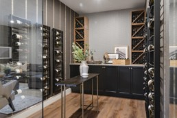 Wine cellar with glass walls and ceiling high wine racks, wood interior design. Pacesetter homes the Ellertston estate home in Jensen Lakes St. Albert.