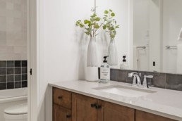 Bathroom with white counters and dark brown wood sink cabinets, plant interior accents. St. Albert Pacesetter showhomes in Jensen Lakes.