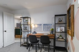 Double desk study area with wood style desk and black wire accents in Ellertson showhome by Pacesetter homes.