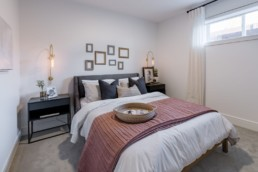 Bedroom with simple pink and grey decor with blank walls and high window, basement bedroom. Pacesetter homes Jensen Lakes.