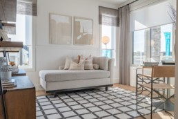Living area with large windows and beige modern interior design in Jensen Lakes showhomes.