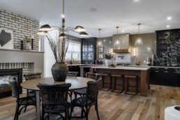 Dining area with kithen with wooden and wicker style furniture, white counterstops and grey tile backsplash in Pacesetter Augusta Executive estate collection in Jensen Lakes St. Albert.
