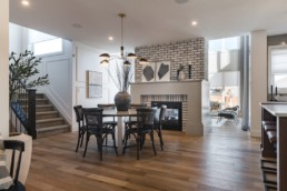Dining area with grey brick wall and black wicker chairs with grey interior classy design in Jensen Lakes Pacesetter Showhomes.