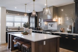 Kitchen with leather brown stools, white countertops and grey backsplash tile, modern design for spacious living in Jensen Lakes Estate homes in St. Albert