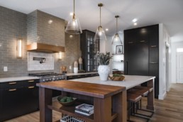 Kitchen with white stone counter and grey backsplash, mid century modern style light fixtures. Showhome by Pacesetter homes Augusta Executive collection in Jensen Lakes.