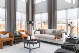 Living room with ceiling high windows and orange with grey luxurious spacious design. Executive collection by Pacesetter homes in Jensen Lakes St. Albert.