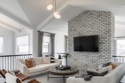 Upstairs loft with white and grey brick wall, grey couches and dark gold accent couch cusions. The ellerston showhome by Pacesetter homes in St. Albert Jensen Lakes.