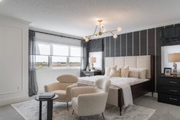 Owner's suite in Ellerston estate home by Pacesetter Homes. White and beige with black accent wall, off white luxurious design in Jensen Lakes.