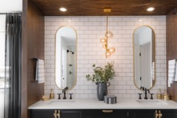Large oval mirrors with gold trip in double sink bathroom. Pacesetter Estate homes in Jensen Lakes.