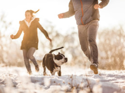 Man running with his dog on a snow while woman is in the background.