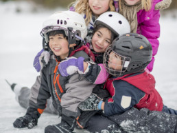 A group of children are huddled in a group on the ice and are wearing snow cloths and ice skates.