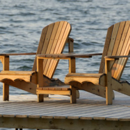 Two wooden beach chairs sit on dock overlooking lake with golden sunlight