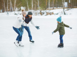 Mother and father skate with son on frozen lake in Jensen Lakes Community