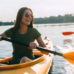 Smiling laughing woman Kayaking in the sunshine on a lake with sunglasses on.