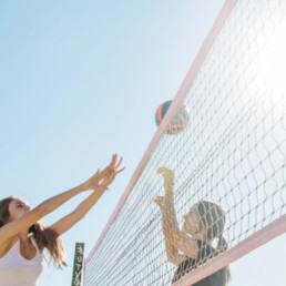 Two girls playing beach volley ball outside in the sunshine on a beach both reaching up with their arms above their heads.
