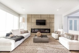 Living room in Onyx showhome in Jensen Lakes St. Albert, Kanvi homes. Concrete accent wall with spacious couches and luxurious white interior design.