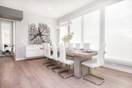 The Onyx showhome by Kanvi homes dining room with white and light grey wood toned design. Luxurious living in Jensen Lakes St. Albert.