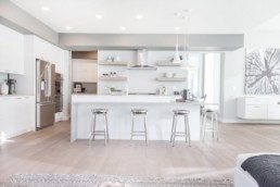 Open concept kitchen with white interior design and silver monochromatic stools. Live luxuriously in Jensen Lakes St. Albert. Kanvi Homes.