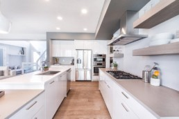 The onyx showhome white spacious modern kitchen with steel appliances in Jensen Lakes by Kanvi Homes St. Albert.