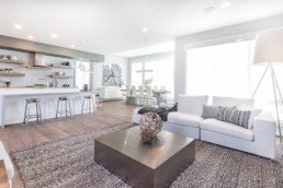 Living room with modern minimal decor and white with grey accents. Spacious living in Jensen lakes with Kanvi Homes St. Albert.