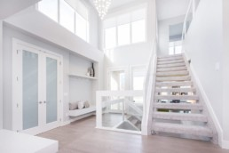 White trimmed staircase with white trim and ceiling high windows, grand area. Showhomes in St. Albert Jensen Lakes.