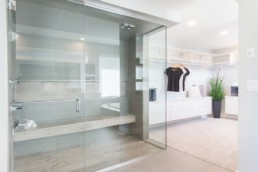 Large glass lined shower connected to spacious walk in closet with white and grey minimalist design in Jensen Lakes. Homes by Kanvi in St. Albert.