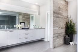 Double sink bathroom with grey wood accent wall and white cabinets. Located in Kanvi showhomes in Jensen Lakes the Onyx.