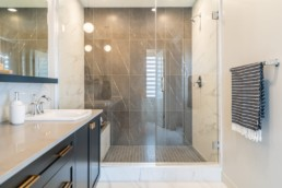 Bathroom shower with glass doors and grey stone, paired with white marble floor. Showhome in Jensen Lakes.