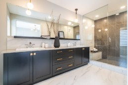 Double sink bathroom with black and gold cabinets. Glass lined shower with marble floors in Pacesetter Calypso showhome in Jensen Lakes St. Albert