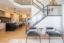 Main floor area with black railing staircase, gold accented kitchen with white walls and modern design. In Jensen Lakes showhomes. The Calypso by Pacesetter homes in St. Albert.