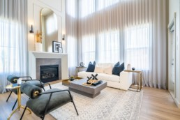 Great room with ceiling high windows and stone lines fireplace. Gold and grey accent decor with white furniture. In Pacesetter homes Calypso showhome in St. Albert's Lakeside living community of Jensen Lakes.